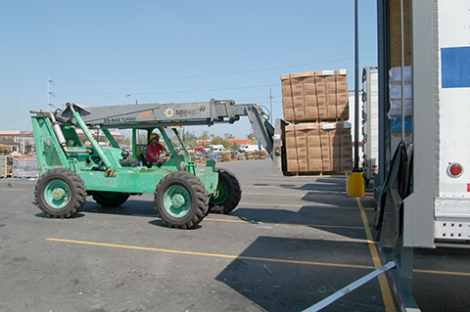 New Orleans, September 7, 2005 - A forklift operator removes two pallets of drinking water from the cargo bay of one of the 20 tractor-trailer units filled with supplies for distribution to individuals at a center set up on Airline Highway. Each unit comntained mkore than 25 tons of ice, water or other life-sustaining supplies for those affected by Hurricane Katrina. Photo by Win Henderson / FEMA photo.